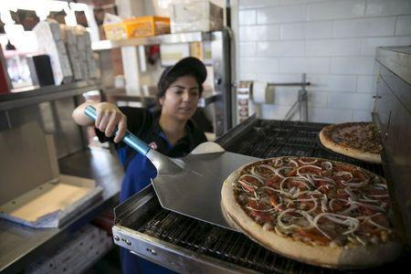 """A worker takes a vegan pizza out of the oven at a Domino's Pizza restaurant in Tel Aviv, Israel July 16, 2015. A growing trend has transformed Israel's financial center into a haven for meatless cuisine. Some 400 food establishments are certified """"vegan friendly,"""" including Domino's Pizza, the first in the global chain to sell vegan pizza topped with non-dairy cheese. REUTERS/Baz Ratner"""
