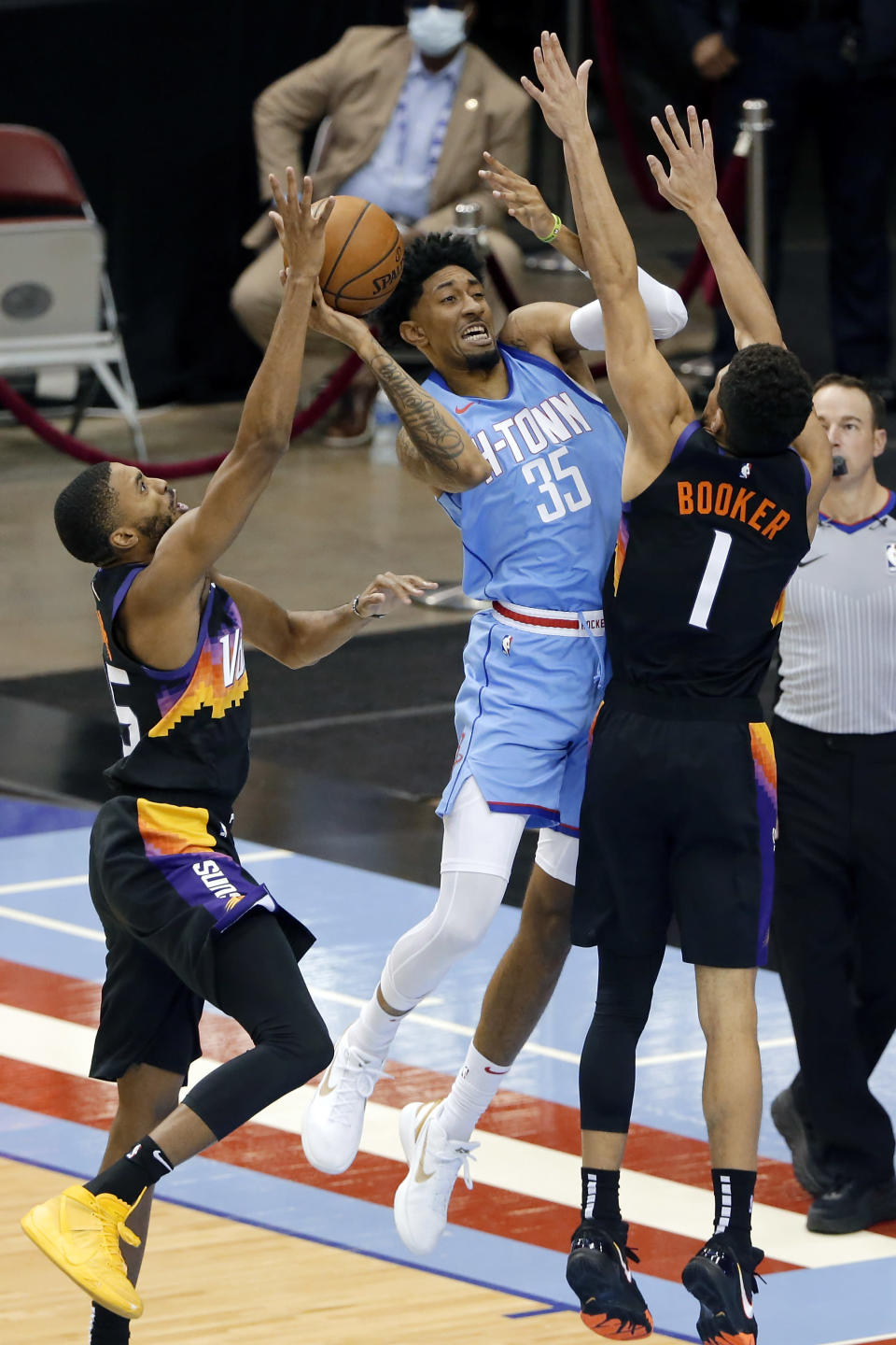 Houston Rockets center Christian Wood (35) shoots between Phoenix Suns forward Mikal Bridges, left, and guard Devin Booker (1) during the second half of an NBA basketball game Wednesday, Jan. 20, 2021, in Houston. (AP Photo/Michael Wyke)