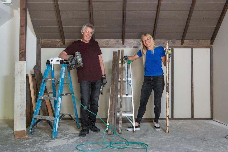 Barry Williams (Greg) and host Jasmine Roth pose after installing old wood planks, salvaged from the basement, to recreate the decor of Greg's attic in the original Brady House. (Photo: Gilles Mingasson/Getty Images)