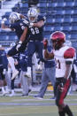 Diego State running back Chance Bell (21) walks off the field as Nevada running back (3) Jamaal Bell and defensive end Sam Hammond celebrate their win in an NCAA college football game Saturday, Nov. 21, 2020, in Reno, Nev. (AP Photo/Lance Iversen)
