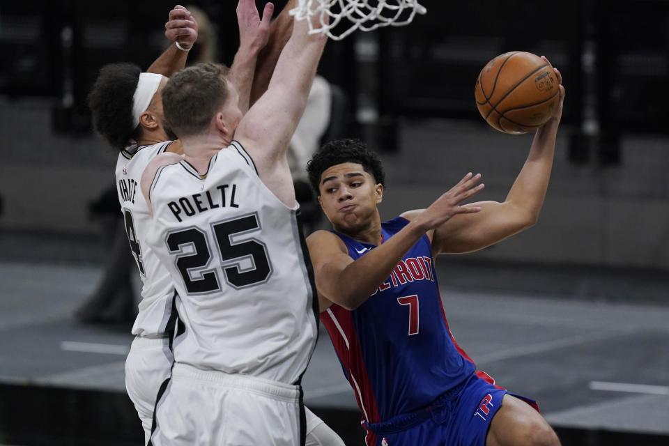 Detroit Pistons guard Killian Hayes (7) drives to the basket against San Antonio Spurs center Jakob Poeltl (25) and guard Derrick White (4) during the second half of an NBA basketball game in San Antonio, Thursday, April 22, 2021. (AP Photo/Eric Gay)