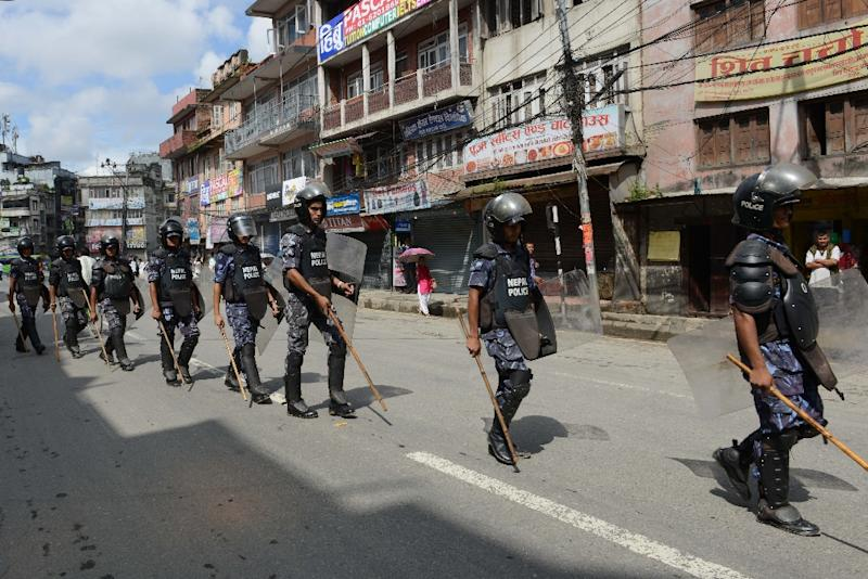 Nepalese police in riot gear walk past shuttered shops during a strike called by the Nepal Federation of Indigenous Nationalities (NEFIN) demanding secularism in the new constitution, in Kathmandu on August 23, 2015 (AFP Photo/Prakash Mathema)