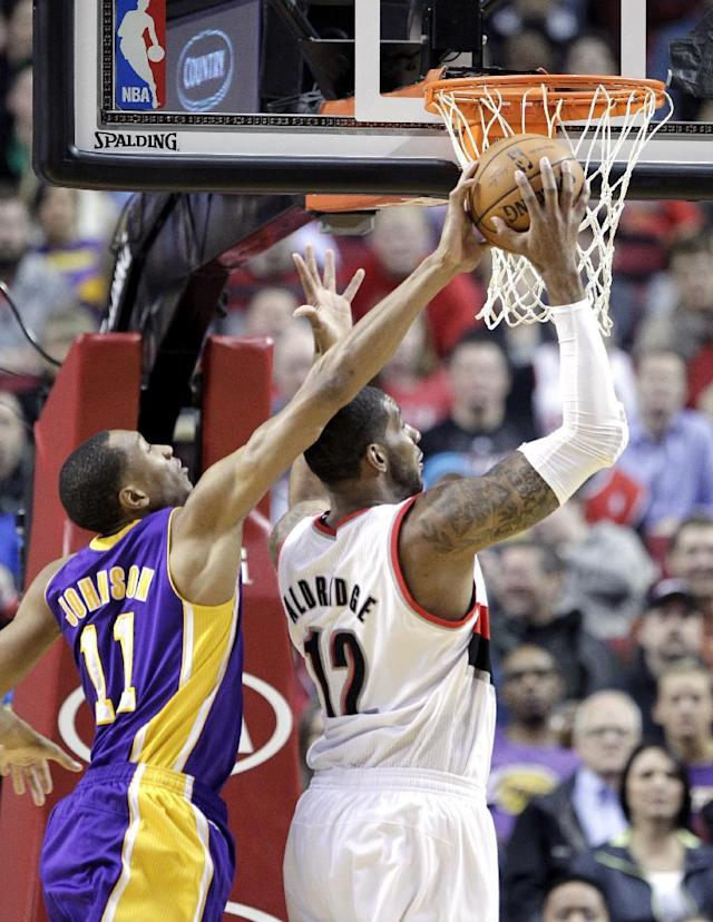Los Angeles Lakers forward Wesley Johnson, left, blocks a shot attempt by Portland Trail Blazers forward LaMarcus Aldridge during the first half of an NBA basketball game in Portland, Ore., Monday, March 3, 2014. (AP Photo/Don Ryan)