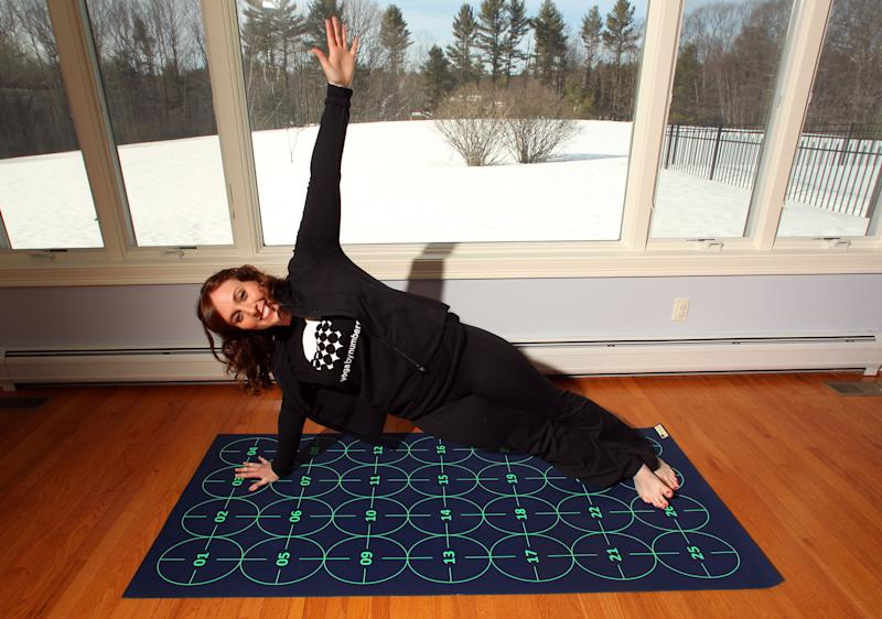 In this March 7, 2014 photo, Elizabeth Morrow poses on her specially designed Yoga by Numbers mat in Bow, N.H. The mat gives true yoga beginners a step-by-step roadmap to learn poses at their own pace. (AP Photo/Jim Cole)