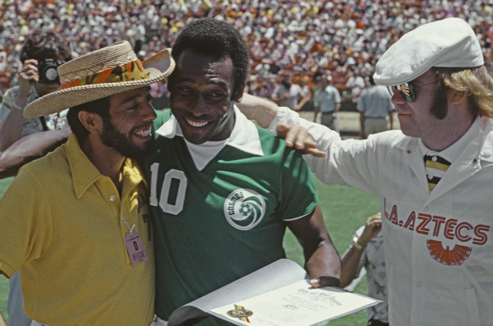 From left to right, musician Sergio Mendes, soccer player Pelé of the New York Cosmos and singer Elton John in Los Angeles, before the start of a North American Soccer League game with the Los Angeles Aztecs, 2nd July 1977. Pele was also given the game ball, and honorary citizenship of the City of Los Angeles. (Photo by Richard Creamer/Michael Ochs Archives/Getty Images)