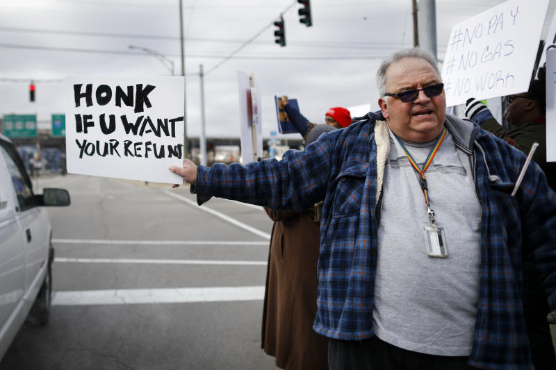 In this Jan. 10, 2019, photo, Will Kohler, an IRS tax examiner, holds a protest sign as union members and other federal employees rally to call for an end to the partial government shutdown outside the IRS site, in Covington, Ky. Kohler applied for unemployment after getting furloughed but said his application is in limbo because the Treasury Department office that needs to verify his claim is closed as a result of the shutdown. (AP Photo/John Minchillo)