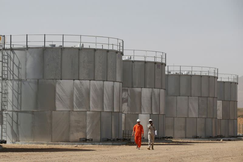 FILE PHOTO: Workers walk past storage tanks at Tullow Oil's Ngamia 8 drilling site in Lokichar