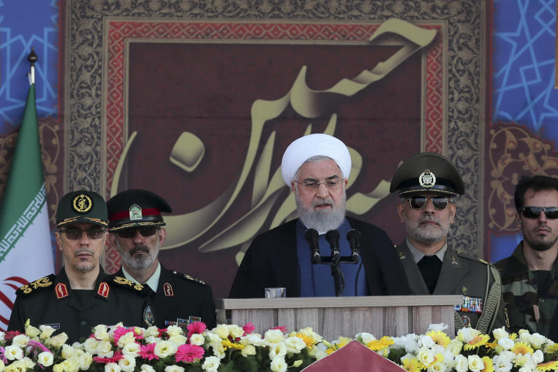 In this photo released by the official website of the office of the Iranian Presidency, President Hassan Rouhani speaks at a military parade marking 39th anniversary of outset of Iran-Iraq war, in front of the shrine of the late revolutionary founder Ayatollah Khomeini, just outside Tehran, Iran, Sunday, Sept. 22, 2019. Chief of the General Staff of the Armed Forces Gen. Mohammad Hossein Bagheri stands at left. (Iranian Presidency Office via AP)