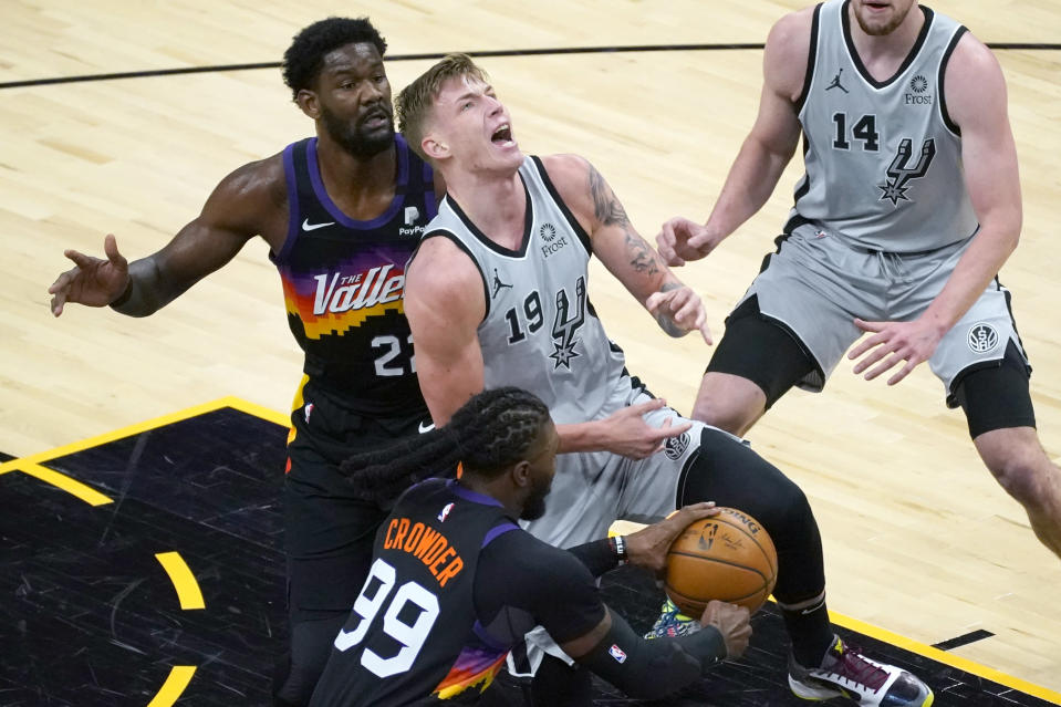 Phoenix Suns forward Jae Crowder (99) strips the ball from San Antonio Spurs forward Luka Samanic (19) as center Deandre Ayton (22) defends during the first half of an NBA basketball game Saturday, April 17, 2021, in Phoenix. (AP Photo/Rick Scuteri)