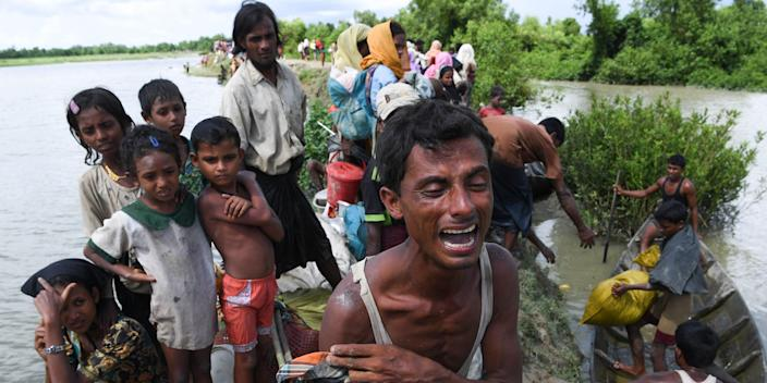 Graphic content / In this picture taken on October 9, 2017, a Rohingya refugee reacts while holding his dead son after crossing the Naf river from Myanmar into Bangladesh in Whaikhyang. - A top UN official said on October 7 Bangladesh's plan to build the world's biggest refugee camp for 800,000-plus Rohingya Muslims was dangerous because overcrowding could heighten the risks of deadly diseases spreading quickly. The arrival of more than half a million Rohingya refugees who have fled an army crackdown in Myanmar's troubled Rakhine state since August 25 has put an immense strain on already packed camps in Bangladesh. (Photo by Indranil MUKHERJEE / AFP) (Photo credit should read INDRANIL MUKHERJEE/AFP via Getty Images)