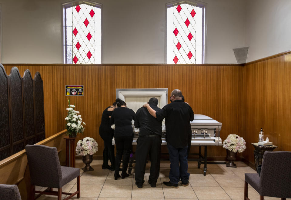 EAST LOS ANGELES, CA - DECEMBER 20: Family members gather to mourn Edith Fernandez alongside her casket at the Continental Funeral Home on Sunday, Dec. 20, 2020 in East Los Angeles, CA. The 47-year-old died Dec. 8, 2020 from complications of Covid-19. (Brian van der Brug / Los Angeles Times via Getty Images)