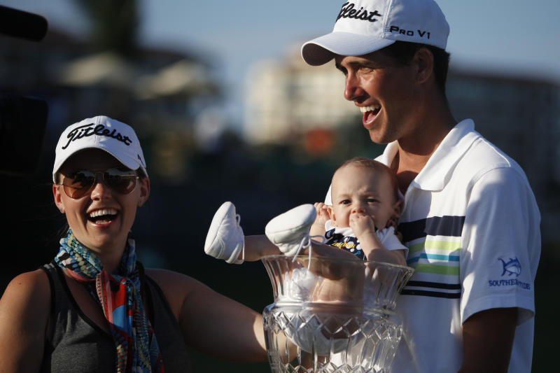 U.S.' Chesson Hadley celebrates with his wife Amanda and his newborn son Hughes, who sits in his trophy, after winning the Puerto Rico Open PGA golf tournament in Rio Grande, Puerto Rico, Sunday, March 9, 2014. (AP Photo/Ricardo Arduengo)