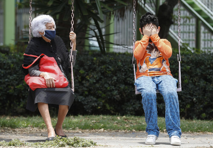 A woman and boy sit on a set of swings as they wait for the all-clear to return to their apartment, after an earthquake in Mexico City, Tuesday, June 23, 2020. The earthquake struck near the Huatulco resort in southern Mexico on Tuesday morning, swayed buildings in Mexico City and sent thousands fleeing into the streets. (AP Photo/Eduardo Verdugo)