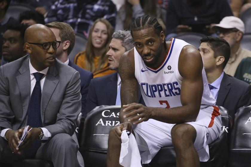 Clippers assistant coach Sam Cassell, left, sits with Kawhi Leonard during a loss to the Suns on Oct. 26, 2019, in Phoenix.