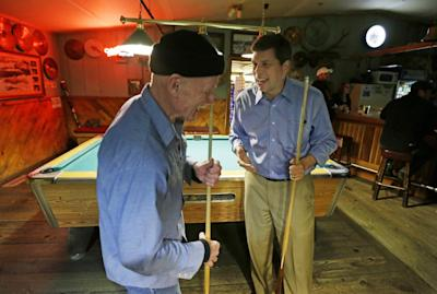 In this Oct. 10, 2014 photo, U.S. Sen. Mark Begich, right, D-Alaska, jokes with Jimmy Maddox, left, after Maddox challenged the senator to a game of pool at Kito's Kave, a bar in Petersburg, Alaska. Begich had stopped at the bar to get a late-night burger after a full day of campaigning. (AP Photo/Ted S. Warren)