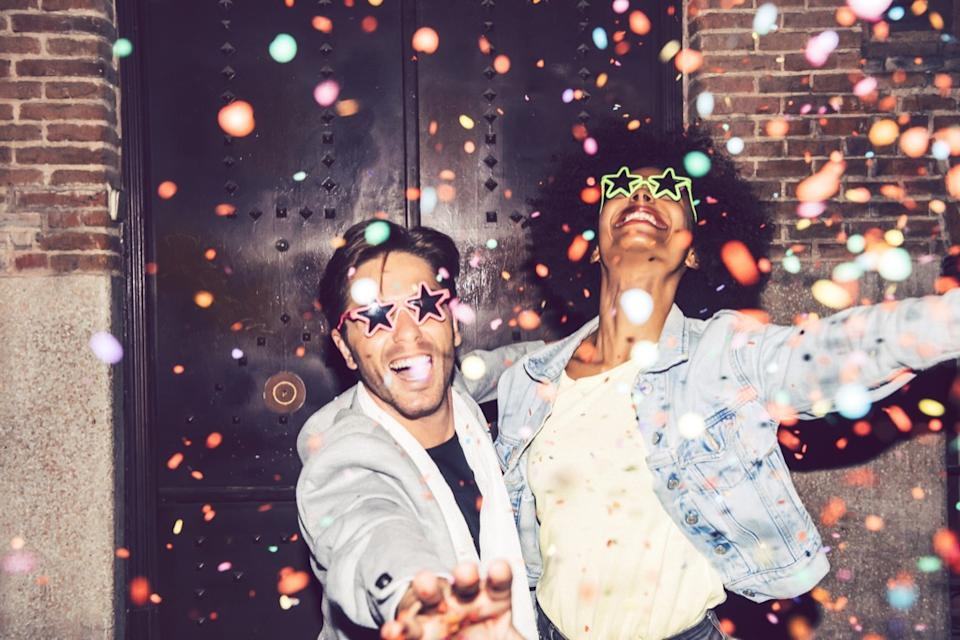man and woman wearing fun glasses with confetti