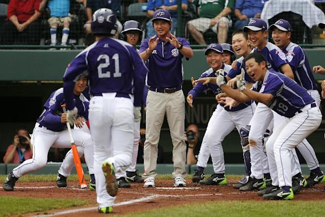 CORRECTS DATE AND YEAR TO AUG. 20, 2014 - Seoul's Jae Yeong Hwang (18) is greeted by teammates after hitting a solo home run off Tokyo pitcher Suguru Kanamori in the sixth inning of a International semi-final baseball game against Tokyo at the Little League World Series tournament in South Williamsport, Pa., Wednesday, Aug. 20, 2014. (AP Photo/Gene J. Puskar)