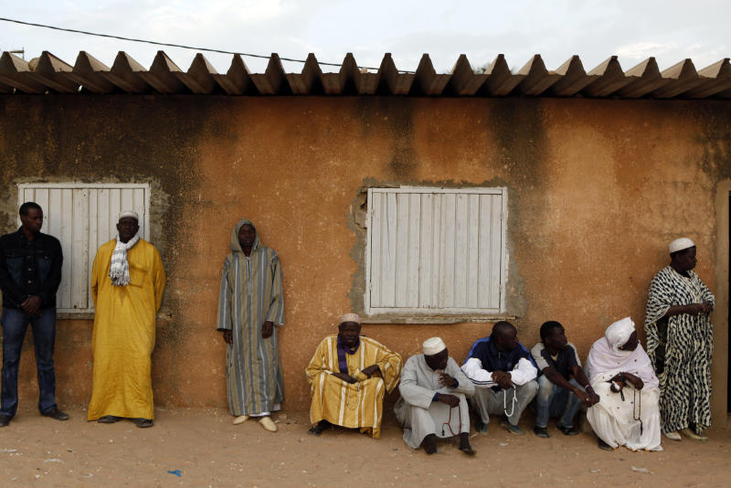 Men and a woman hold Muslim prayer beads as they wait for a polling station to open, in the Cambarene neighborhood of Dakar, Senegal on Sunday, Feb. 26, 2012. After weeks of riots, Senegalese voters began casting their ballots Sunday in an election that threatens the country's image as one of the oldest and most robust democracies in Africa. This normally unflappable nation on the continent's western coast has been rocked by back-to-back protests following the decision of its 85-year-old leader Abdoulaye Wade to seek a third term. (AP Photo/Rebecca Blackwell)