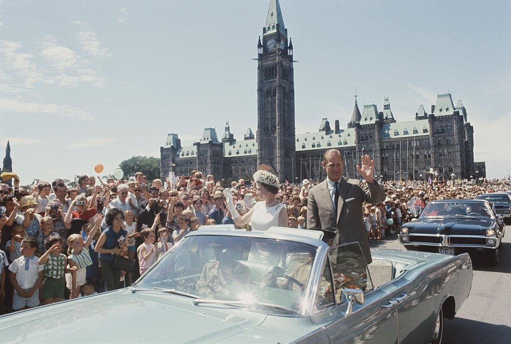 <p>Queen Elizabeth II and Prince Philip wave to spectators on Parliament Hill in Ottawa during a royal tour of Canada in July [Getty/Rolls Press/Popperfoto]<br /></p>