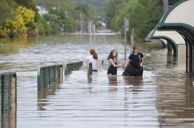 Girls walk through floodwaters as they recede in Lismore. Source: AAP