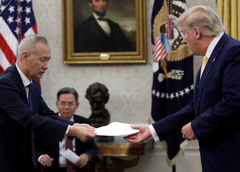 "WASHINGTON, DC - OCTOBER 11: Chinese Vice Premier Liu He presents U.S. President Donald Trump with a letter from Chinese President Xi Jinping after Trump announced a ""phase one"" trade agreement with China in the Oval Office at the White House October 11, 2019 in Washington, DC. China and the United States have slapped each other with hundreds of billions of dollars in tariffs since the current trade war began between the world's two largest national economies in 2018. (Photo by Win McNamee/Getty Images)"