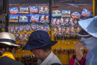 Tourists look at merchandise for sale at a souvenir shop outside of the Jokhang Temple in Lhasa in western China's Tibet Autonomous Region, Tuesday, June 1, 2021. Tourism is booming in Tibet as more Chinese travel in-country because of the coronavirus pandemic, posing risks to the region's fragile environment and historic sites. (AP Photo/Mark Schiefelbein)