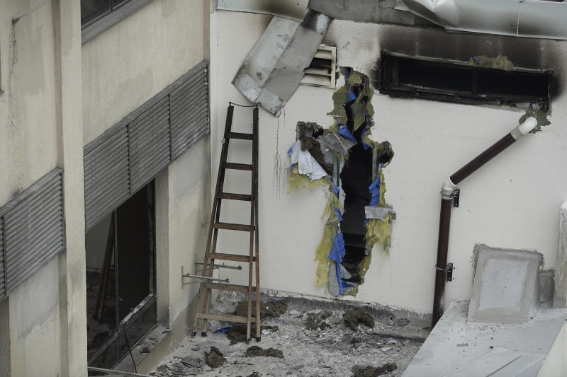 A hole is seen on an outside wall of the Badim Hospital, where a fire left at least 11 people dead, in Rio de Janeiro, Brazil, Friday, Sept. 13, 2019. The fire raced through the hospital forcing staff to wheel patients into the streets on beds or in wheelchairs. (AP Photo/Leo Correa)