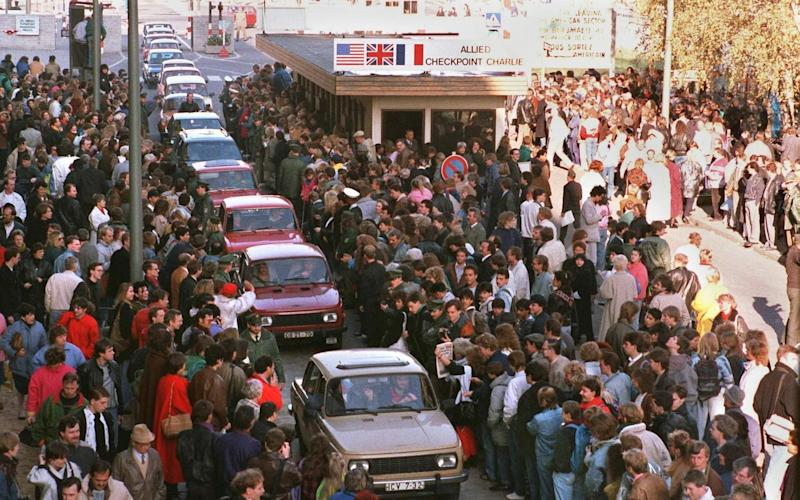 Wartburgs pass through Checkpoint Charlie to be greeted by West Berliners in November 1989 - AFP