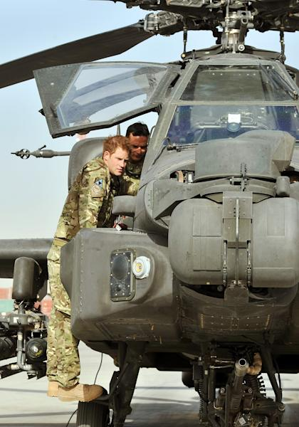 In this Friday, Sept. 7, 2012 photo made available on Sunday, Sept. 9, 2012, Britain's Prince Harry climbs up to examine the cockpit of an Apache attack helicopter with the 30mm cannon below, with a member of his squadron, obscured behind name not provided, at Camp Bastion in Afghanistan, where he starts his tour of duty as a co-pilot gunner. The 27-year-old Army captain Prince Harry, known as Captain Harry Wales, is on his second tour of duty in Afghanistan but will go through the usual familiarization process before becoming operational and flying attack helicopters. (AP Photo/John Stillwell, Pool)