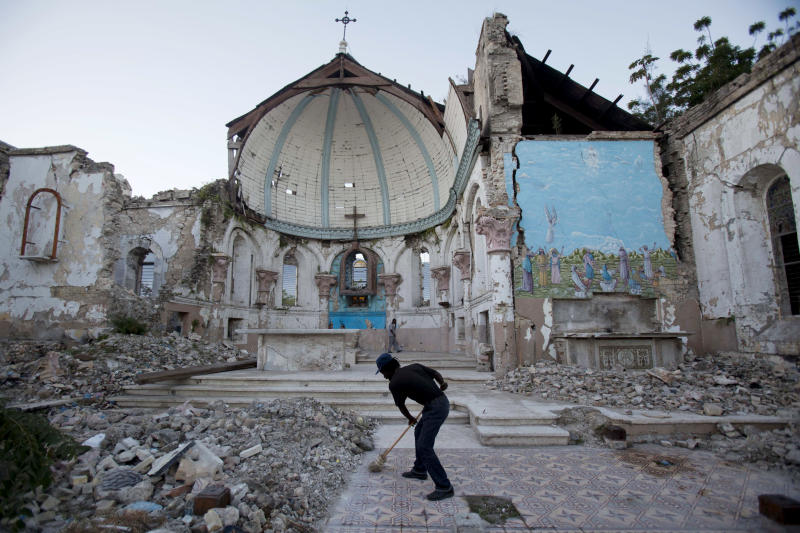"FILE - In this Jan. 12, 2013 file picture a man sweeps an exposed tiled area of the earthquake-damaged Santa Ana Catholic church, where he now lives, in Port-au-Prince, Haiti.   Haiti's prime minister Laurent Lamothe  says his deeply poor country is aiming to attract high-end tourists and multinational investors — instead of constant handouts — to get on its feet after the devastating 2010 earthquake. In an interview with The Associated Press, Lamothe said Saturday Jan. 26, 2013  that ""Haiti is open for business."" He's pushing that idea — and a bid to build up Haiti's tourism industry — in meetings with CEOs at the World Economic Forum in Davos, Switzerland. (AP Photo/Dieu Nalio Chery,File)"