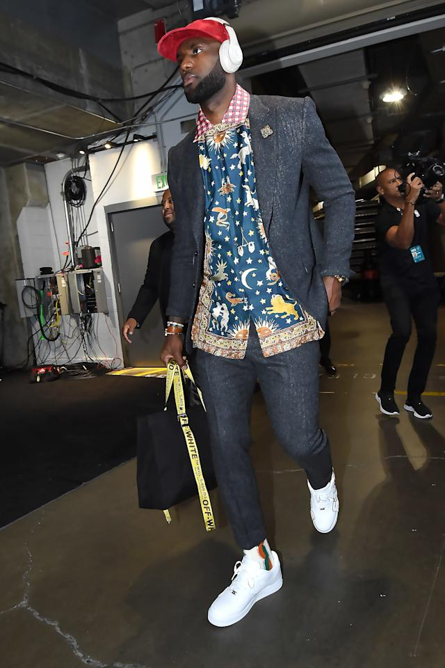 """<p>WHAT: Gucci shirt, Nike sneakers</p> <p>WHERE: The Los Angeles Lakers vs. LA Clippers game in Los Angeles</p> <p>WHEN: October 22, 2019</p> <p>WHY: LeBron James takes the serious gray suit to <a href=""""https://www.gq.com/story/big-fit-of-the-day-10-23-19?mbid=synd_yahoo_rss"""">a far-out place</a>.</p>"""