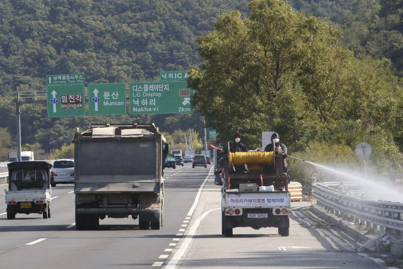 Disinfectant solution is sprayed from a vehicle as a precaution against African swine fever on the road in Paju, South Korea, near the border with North Korea, Tuesday, Oct. 15, 2019. Amid swine fever scare that grips both Koreas, South Korea is deploying snipers, installing traps and flying drones along the rivals' tense border to kill wild boars that some experts say may have spread the animal disease from north to south. (AP Photo/Ahn Young-joon)