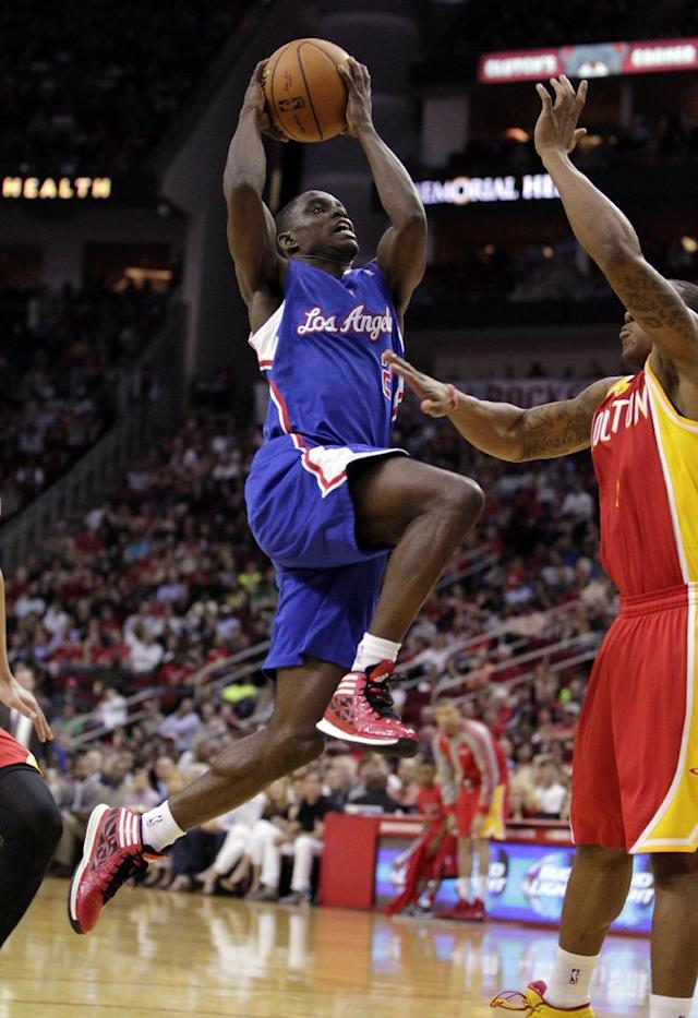 Los Angeles Clippers guard Darren Collison lays the ball up against Houston Rockets guard Isaiah Canaan during the first quarter of an NBA basketball game, Saturday, March 29, 2013, in Houston. (AP Photo/Patric Schneider)
