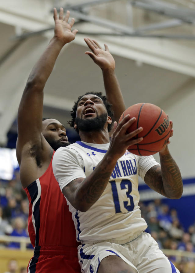 Seton Hall guard Myles Powell (13) drives to the basket past Stony Brook guard Andrew Garcia (23) during the first half of an NCAA college basketball game Saturday, Nov. 9, 2019, in South Orange, N.J. (AP Photo/Adam Hunger)