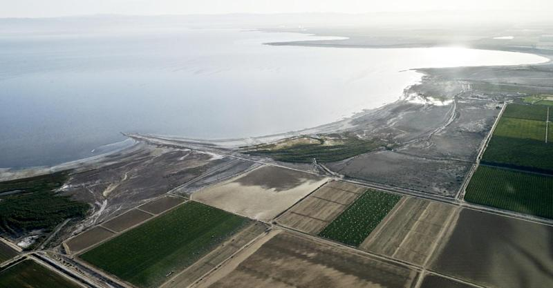 FILE - This May 1, 2015 aerial file photo shows the exposed lake bed of the Salton Sea evaporating near Niland, Calif. California officials have proposed spending nearly $400 million over 10 years to slow the shrinkage of the state's largest lake. Gov. Jerry Brown's administration on Thursday, March 16, 2017 unveiled a plan to build ponds on the northern and southern ends of the Salton Sea. It's expected to evaporate at an accelerated pace starting next year when the San Diego region no longer diverts water to the desert region. (AP Photo/Gregory Bull, File)