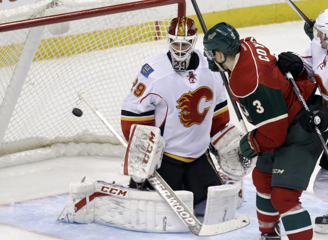Minnesota Wild's Charlie Coyle, right, watches as Jared Spurgeon scores a power play goal on Calgary Flames goalie Reto Berra in the third period of an NHL hockey game, Monday, March 3, 2014, in St. Paul, Minn. The Wild won 3-2. (AP Photo/Jim Mone)
