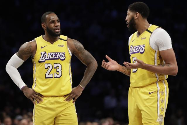 Los Angeles Lakers' LeBron James (23) talks to Anthony Davis (3) during the first half of an NBA basketball game against the Brooklyn Nets Thursday, Jan. 23, 2020, in New York. (AP Photo/Frank Franklin II)