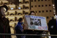An Israeli protester holds a sign with a photo of President Donald Trump, calling for the ouster of Prime Minister Benjamin Netanyahu, shortly after results of the U.S. presidential election were announced, during a protest against Netanyahu in Jerusalem, Saturday, Nov. 7, 2020. Thousands of Israelis protested against Netanyahu, a close ally of Trump, demanding he step down because of his handling of the coronavirus crisis and the corruption charges he faces. (AP Photo/Maya Alleruzzo)