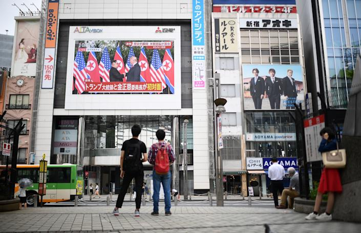 Pedestrians in Tokyo look at a wall-mounted screen displaying live news of the meeting between Trump and Kim on June 12, 2018.