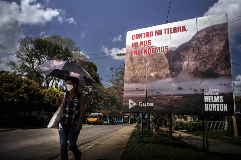"""A woman walks past an anti-embargo sign that reads in Spanish: """"Against my land, we don't understand each other"""" in Viñales, Cuba, March 1, 2021. Both U.S. sanctions meant to punish the government and a COVID-19 pandemic have squashed tourism almost everywhere, making some Cubans hope that new U.S. President Joe Biden will reverse at least some of the restrictions implemented by his predecessor. (AP Photo/Ramon Espinosa)"""