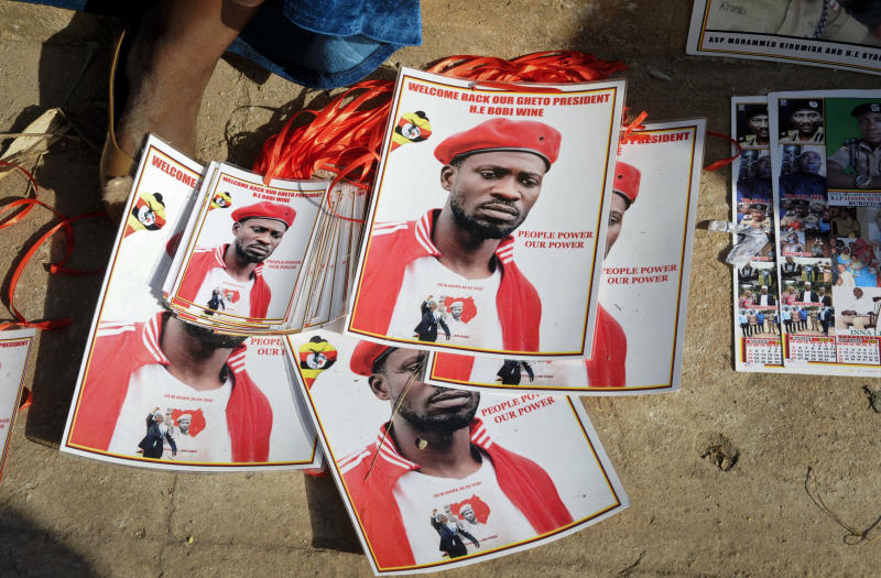 A supporter sits next to posters of pop star-turned-opposition lawmaker Bobi Wine whose real name is Kyagulanyi Ssentamu at his home in Kampala Uganda Thursday Sept. 20 2018. Wine vowed Thursday to continue his fight for more freedom in the country