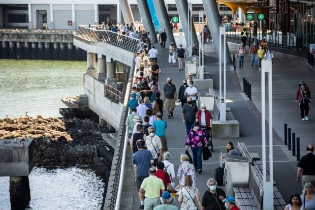 People are pictured waiting in line outside of Canada Place for their COVID-19 vaccination in Vancouver on Monday. (Ben Nelms/CBC - image credit)