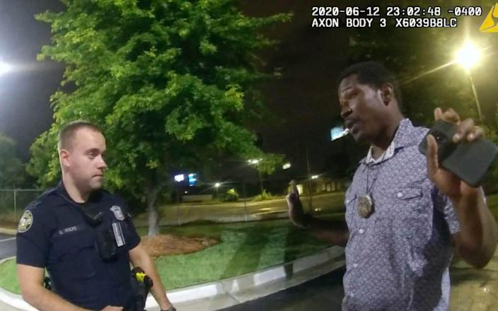 Body camera video provided by the Atlanta Police Department shows Rayshard Brooks speaking with Officer Garrett Rolfe in the parking lot of a Wendy's restaurant, in Atlanta. - AP