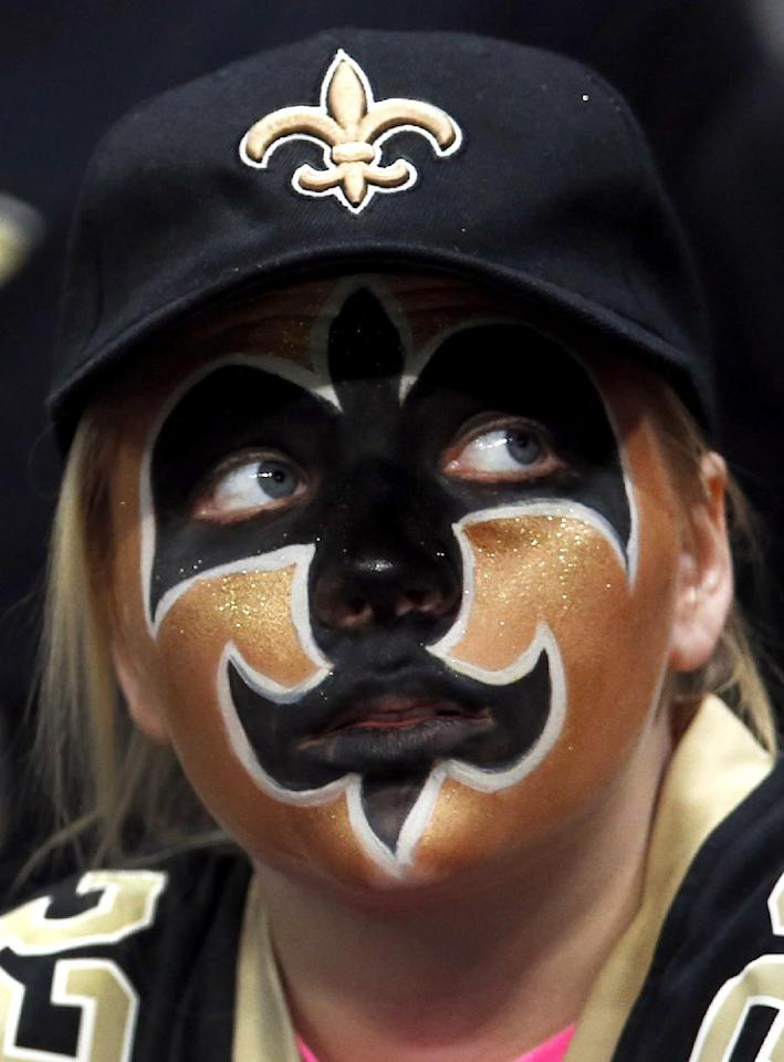 A New Orleans Saints fan sits in the stands during the second quarter of an NFL football game between the St. Louis Rams and the New Orleans Saints, Sunday, Dec. 15, 2013, in St. Louis. (AP Photo/Charles Rex Arbogast)