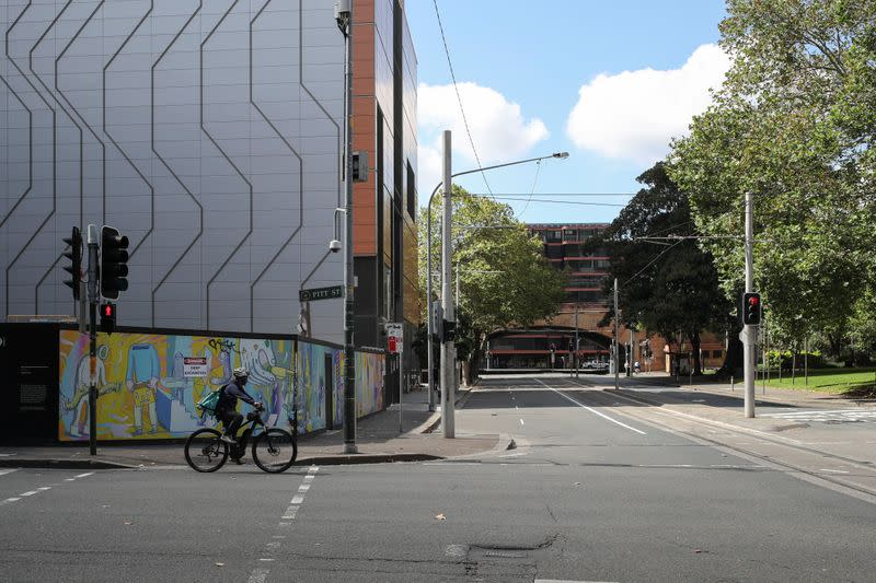 A man rides his bicycle by an almost empty street during a workday following the implementation of stricter social-distancing and self-isolation rules to limit the spread of the coronavirus disease (COVID-19) in Sydney