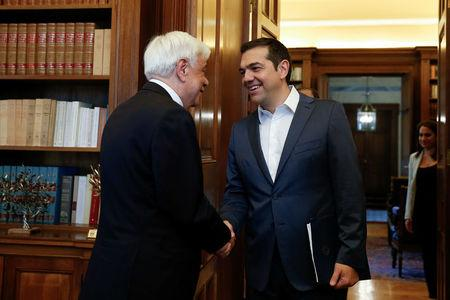 Greek Prime Minister Alexis Tsipras shakes hands with Greek President Prokopis Pavlopoulos before briefing him on developments on the name dispute with Macedonia, in Athens