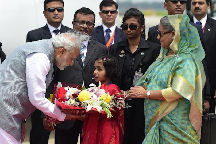 Indian Prime Minister Narendra Modi receives a floral bouquet as Bangladeshi premier Sheikh Hasina Wajid looks on during a ceremony at the Hazrat Shahjalal International Airport in Dhaka, on June 6, 2015 (AFP Photo/Munir Uz Zaman)