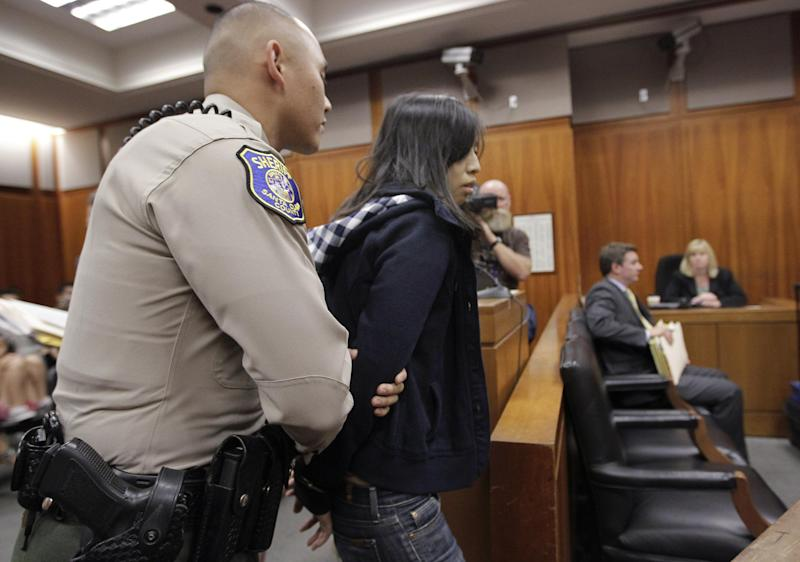 Margaret Ngo is held by a Santa Clara County Sheriff's deputy in a San Jose, Calif., courtroom, Monday, July 16, 2012, as she and three other family members were charged with severely neglecting a dozen mentally disabled adults in their care in an upscale San Jose home. Authorities say inside the house would be the horrific scene of an unkempt, unlicensed care center where a dozen mentally disabled adults were beaten, malnourished and even not allowed to use toilet paper. (AP Photo/Paul Sakuma)