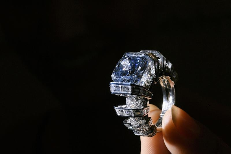 """A model presents the """"The Sky Blue Diamond,"""" a fancy, vivid blue diamond ring created by Cartier, during a press preview by Sotheby's Auction House on November 9, 2016 in Geneva (AFP Photo/Fabrice Coffrini)"""