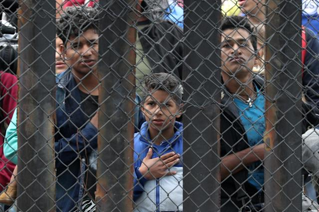<p>Members of a migrant caravan from Central America and their supporters look through the U.S.-Mexico border wall at Border Field State Park before making an asylum request, in San Diego, California, April 29, 2018. (Photo: Lucy Nicholson/Reuters) </p>